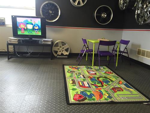 Kid friendly waiting area with TV, Coffee, and coloring books.