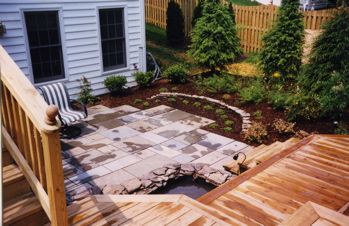 Water feature, patio, plants and deck design and installation by Terra Landscape and Design