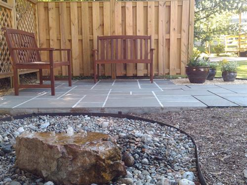 Container plants, patio and water feature by Terra Landscape and Design