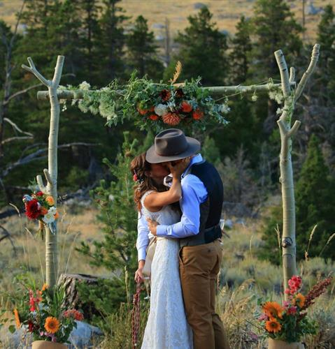 Rustic outdoor wedding ceremony arbor in Sinks Canyon