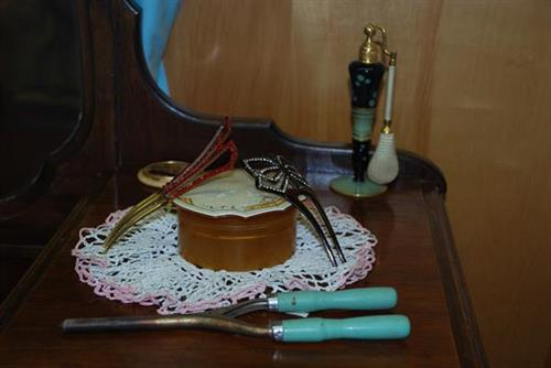Atomizer, decorative hair combs, celluloid powder box, and single-barrel curling iron.