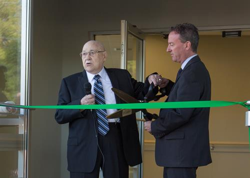 Bill Graves and Mayor Ted Clugston cut the ribbon at the opening of the new 13th Street SE home for people with developmental disabilities who have dementia.