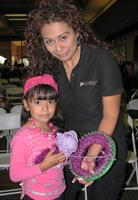 Employee Martha Santillan and daughter Lilly making a hat for HATS FOR HOPE