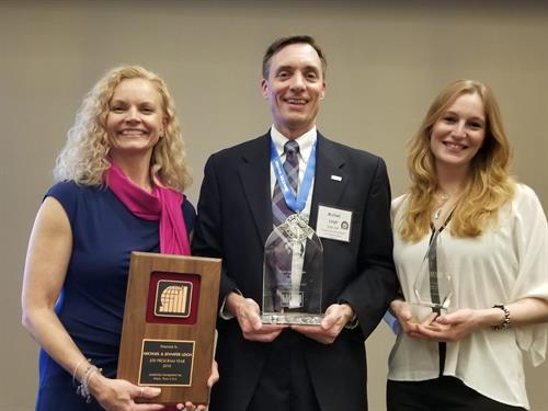Lois James, Mike Leigh, and Beatrice Castellani receiving World Growth Award from LMI, Inc.