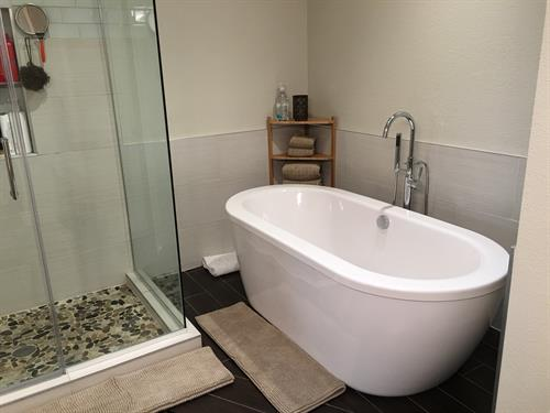 Walk in shower with pebble shower pan with a stand alone tub