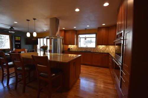 Kitchen remodel with island housing cook top and ceiling hood