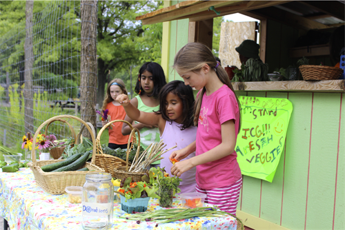 Campers selling produce at our Farm Stand
