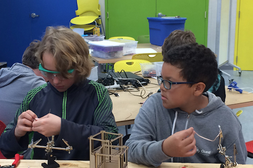 Boys wroking together to build carboard robots