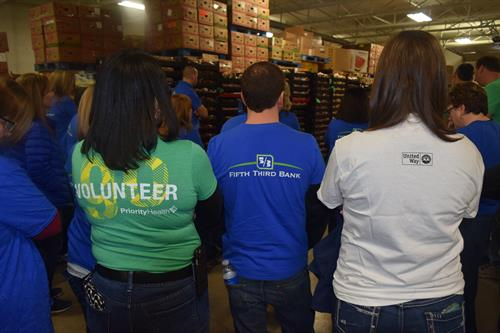 Priority Health and Fifth Third Bank employees volunteering at the Foodbank of Eastern Michigan.