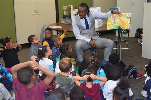 Brandon Carr reading to students at Doyle Ryder Elementary in their new Club Connect Reading Center.