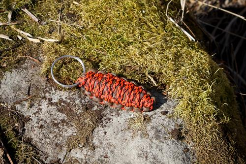 The Fire Bug is a survival pod keychain that includes firesteel, scraper, waterproof jute, knife, and mylar signal mirror and 16 feet of paracord