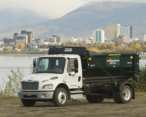 A hook lift truck overlooking Anchorage.