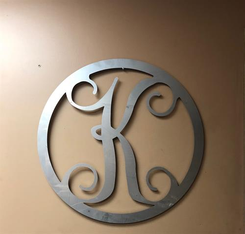 "The possibilities are pretty much endless with laser cutting. Check out this simple circle ""K"" custom made for a customer."