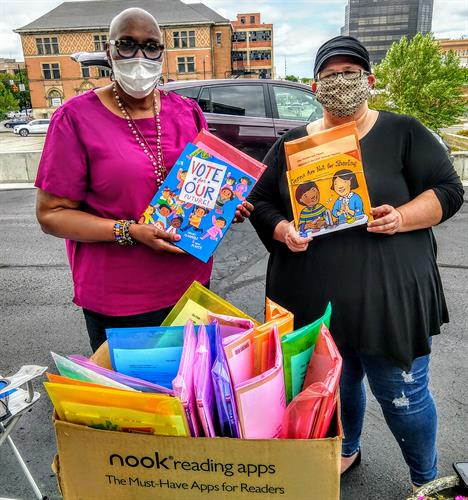 Pastor Cynthia & Pastor Heather handing out books for LEAP, summer reading program