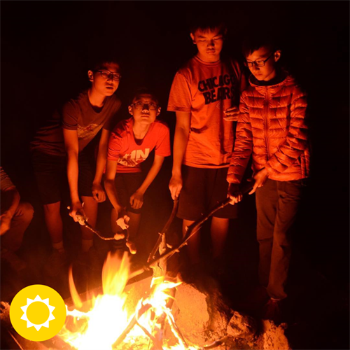 Summit Academy students and friends enjoying a campfire experience together.
