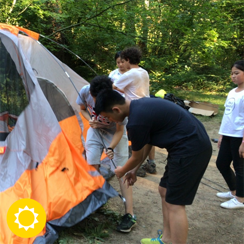 Summit Academy students learning how to pitch a camping tent.
