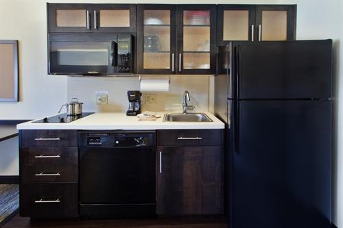 Full Kitchen with microwave, full size refrigerator, dishwasher, stove top, pots/pans, utensils, and dishes.