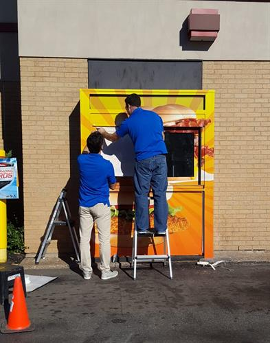 A few FASTSIGNS installers wrapping a drive-thru window.