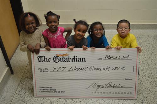 The Guardian presents large cheque from Raise-a-Reader Champaign to children during one of the Alliance's Literacy Camp.