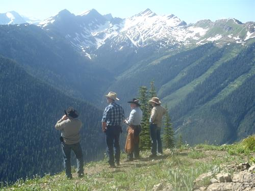 Summer pack trip guests taking in stunning views of the Bob Marshall Wilderness