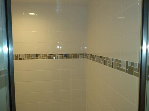 Removed old tiles, opened entry way slightly and then installed new tiles, and glass door to this shower area.