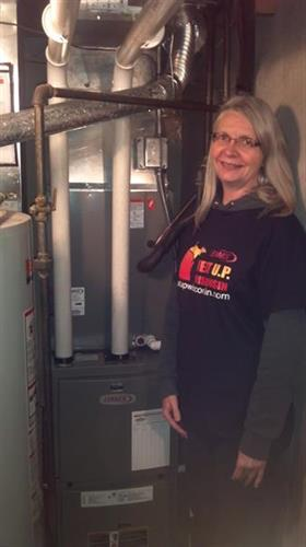 "Cheryl Brock stands with her new Lennox furnace and coil installed by Accu-Clime Mechanical Services LLC.  Cheryl was awarded a new furnace and installation through Heat Up Wisconsins ""People helping people"" program that awards families in need with a free installed furnace.  The furnace is donated by Lennox while the labor and materials are donated by the local dealer."