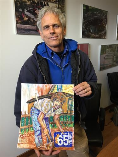 Paul Ganshert proudly holds a special anniversary portrait for their office and social media marketing.