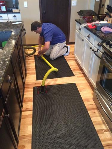 Installing drying mats to dry hard wood floors from a water loss
