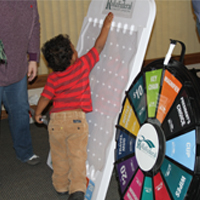 A young RFCU member tries his hand at plinko at our 2012 International Credit Union Day.
