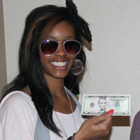 An RFCU member displays her winnings from playing plinko at our 2012 International Credit Union Day.