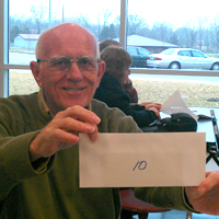An RFCU member shows off his $10 cash prize at our 2013 annual meeting.