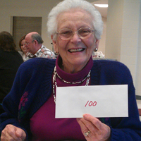 An RFCU member shows off her $100 cash prize at our 2013 annual meeting.