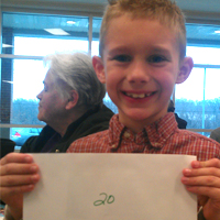 A young RFCU member shows off his $20 cash prize at our 2013 annual meeting.