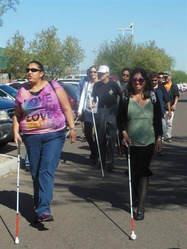Clients walking to the light rail with white canes showing