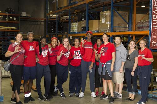 University of Arizona Women's Basketball volunteering in the warehouse
