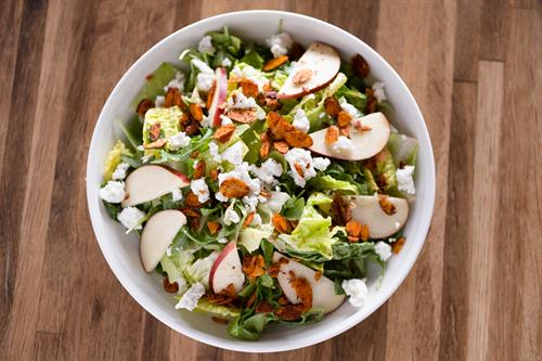 Mixed greens salad with seasonal fruit, goat cheese, candied almonds, and maple vinaigrette at Luigi's West End Pizzeria