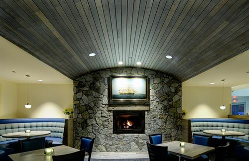 Cozy dining area with fireplace.  Looks like a ship!