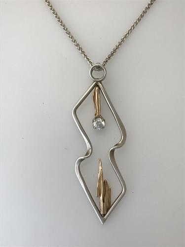 A sterling silver & 14k yellow gold pendant handcrafted by Zack Johnson.