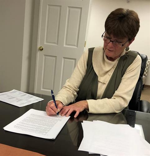 Peg LaCour signing her mortgage and officially becoming a homebuyer and homeowner