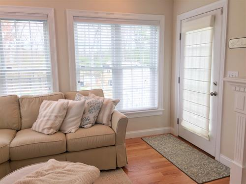 Feel free to mix faux wood blinds with a roman shade on the door to the patio!