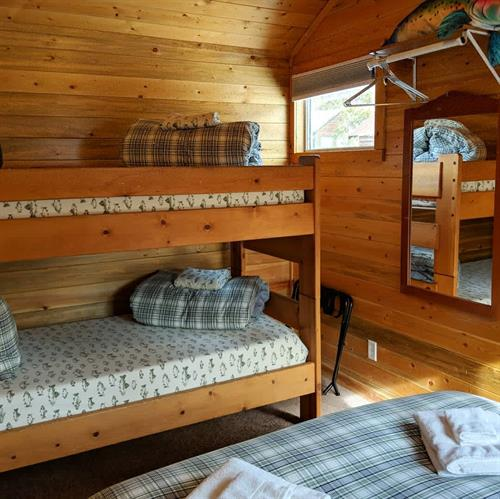 Cabins #4, #5, & #6 all feature a queen bed and bunk bed in the bedroom