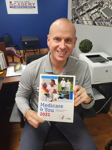 Gallery Image Me_holding_2021_Medicare_and_you_book.JPG