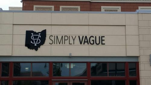 Dimensional lettering helps Simply Vague be seen on a busy street with other shops.