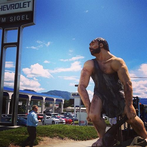 Caveman in front of dealership