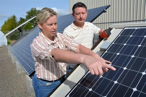 Electronics Instructor Ann Trausch examining a solar panel.