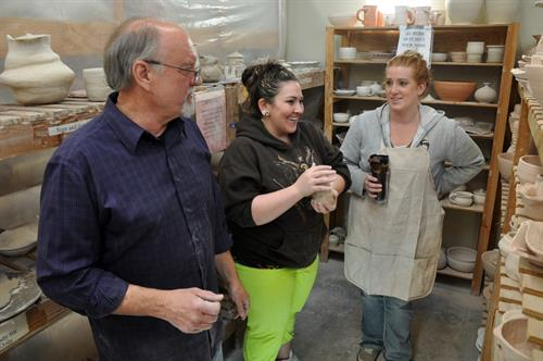 RCC's Pottery instructor assisting students.