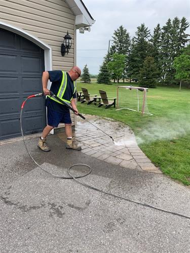NeverBinCleaner power washes walkways to rid of weeds and grass