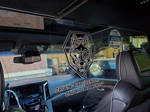 "SUV Interior with custom made ""Plexi Barrier"" to help keep a safe environment for client or guest while traveling."
