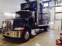 A new straight truck is shown in the garage at Teddy's Transport.