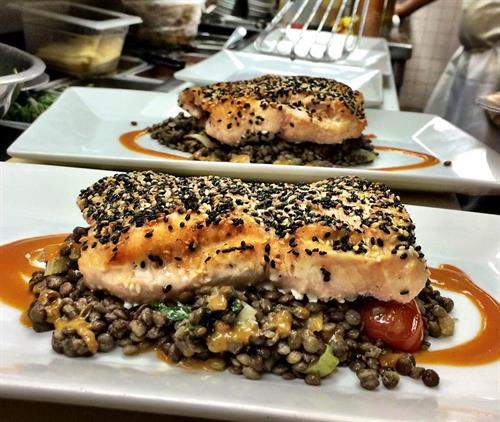 Black and white sesame crusted Atlantic salmon with warm green lentils and roasted tomato coulis